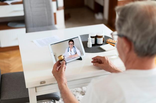 Gros plan sur un vieil homme parlant à un médecin en ligne