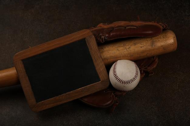 Gros plan sur une vieille balle de baseball, une batte en bois, un gant vintage en cuir usé et un tableau noir sur fond marron foncé grunge, vue de dessus surélevée, directement au-dessus