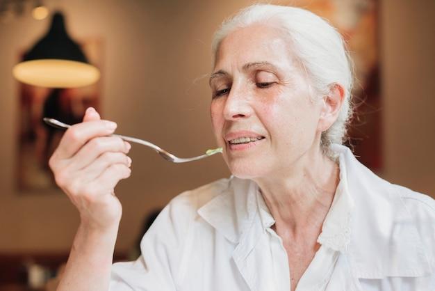Gros plan vieille femme mangeant au restaurant