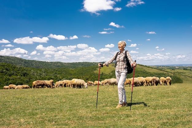 Gros plan d'une vieille femme en randonnée sur les prairies de montagne