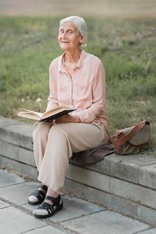 Gros plan vieille femme tenant livre