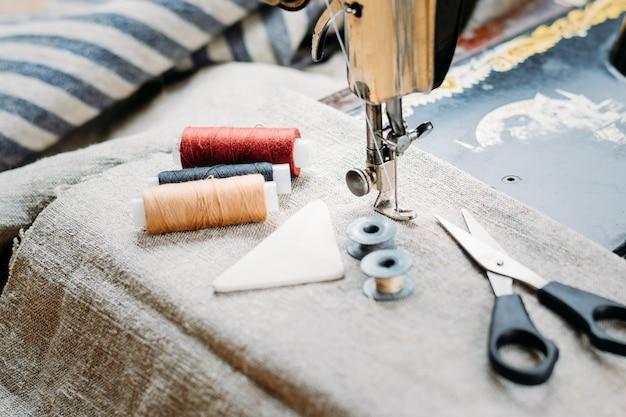 Gros plan de la vieille machine à coudre main vintage, outils de couture et accessoires
