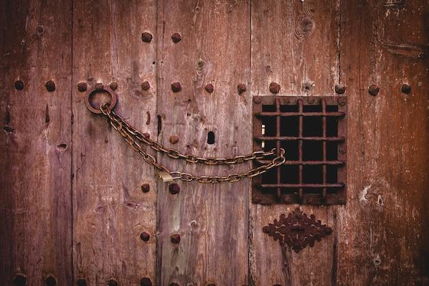 Gros plan d'une vieille serrure à chaîne rouillée sur une grande porte en bois avec une petite clôture en métal