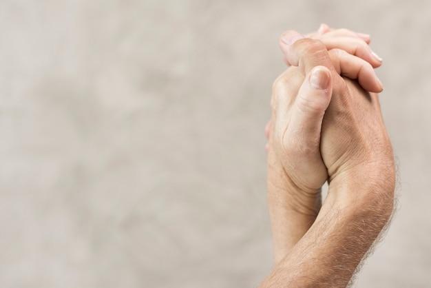 Gros plan vieux couple main dans la main avec un arrière-plan flou