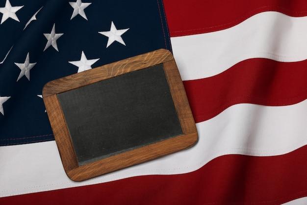 Gros plan sur un vieux panneau de craie en ardoise vintage dans un cadre en bois sur fond de drapeau national américain brodé en coton, symbole du patriotisme américain, vue en grand angle surélevée, directement au-dessus