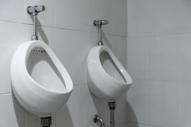 Gros plan de vieux urinoirs dans les toilettes
