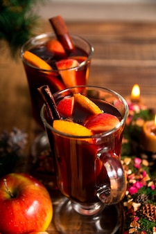 Gros plan de vin chaud de noël avec des fruits, des bougies et des épices
