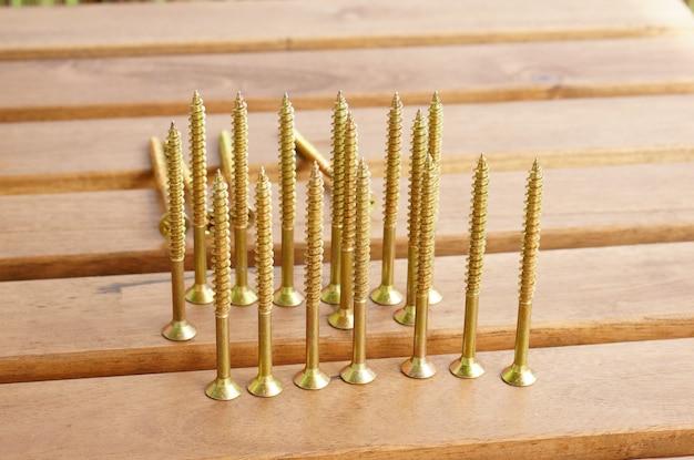 Gros plan de vis croix dorées sur une table dorée