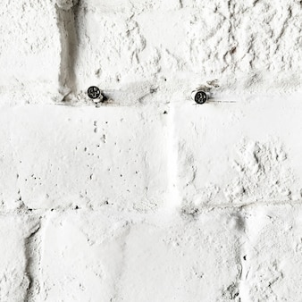 Gros plan de vis sur le mur de briques blanches en béton