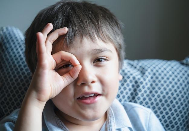 Gros plan sur le visage d'un enfant heureux regardant à travers les doigts dans la caméra avec un visage souriant, un enfant positif montrant un signe avec les mains, une photo d'enfants heureux et mignons s'amusant à jouer à la maison.