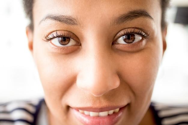 Gros plan de visage féminin africain avec des yeux gentils