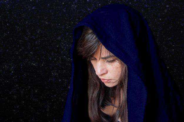 Gros plan sur le visage d'une femme dans un châle bleu foncé, souffrance, tristesse, tristesse. le concept de tragédie ou de tristesse