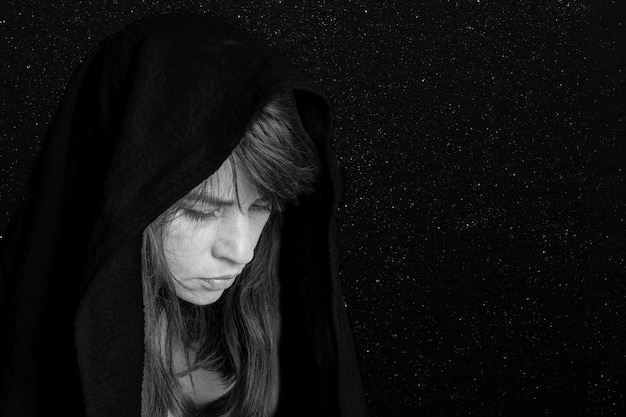 Gros plan sur le visage d'une femme dans un foulard noir, souffrance, tristesse, tristesse. noir et blanc. concept de tragédie ou de tristesse
