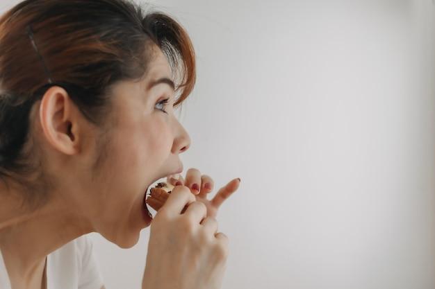 Gros plan visage de femme mordre un morceau de pain sur fond blanc