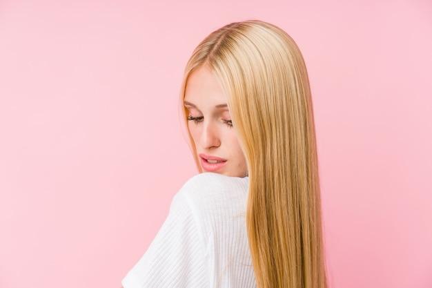 Gros plan de visage de jeune femme blonde isolé sur fond rose