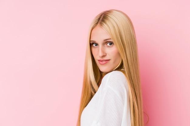 Gros plan visage de jeune femme blonde isolé sur un mur rose