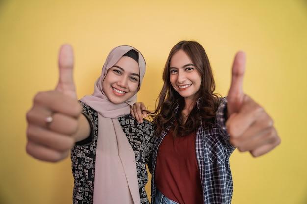 Gros plan des visages de deux femmes souriantes regardant la caméra avec un geste de pouce levé