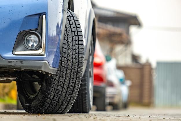 Gros plan d'une voiture garée sur une rue de la ville avec de nouveaux pneus en caoutchouc d'hiver.