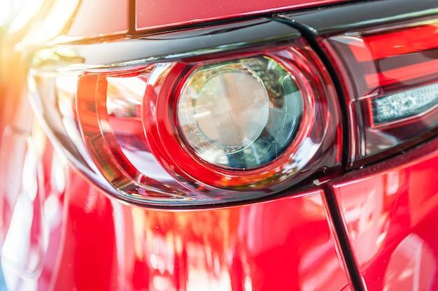 Gros plan d'une voiture de sport rouge au coucher du soleil
