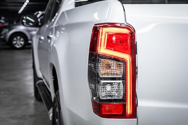 Gros plan sur l'une des voitures de croisement modernes blanches à feux arrière à del rouges. détail extérieur automobile.