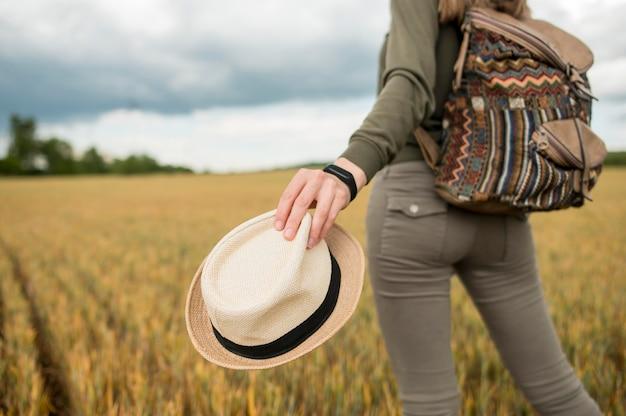 Gros plan voyageur avec sac à dos tenant un chapeau