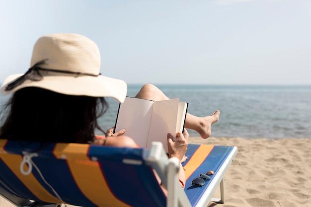Gros plan, vue arrière, femme, plage, lecture, chaise