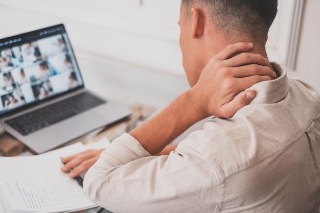 Gros plan, vue arrière, stressé, jeune homme touchant le bas du cou, ressentant une gêne, souffrant d'une douleur soudaine due à un mode de vie sédentaire ou à un long surmenage informatique dans une posture incorrecte au bureau à domicile.