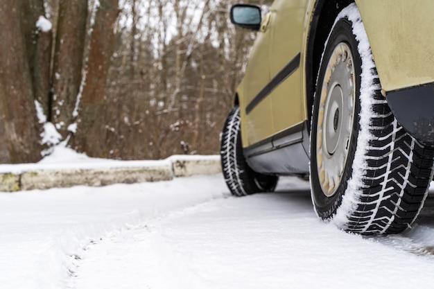 Gros plan sur la vue arrière d'une voiture familiale sur le parking. pneu de roue arrière sale sur la neige. stock photo.