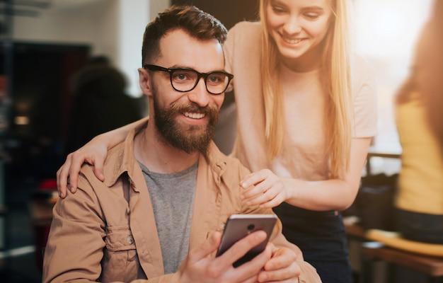 Gros plan et vue en coupe d'un homme barbu en veste assis dans un café confortable à la table et tenant un téléphone à la main. la jeune fille se tient à côté de lui et regarde le téléphone.