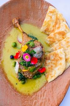 Gros plan vue de dessus de la soupe au poulet au curry avec naan, décorée avec des fleurs et des pétales colorés. art alimentaire.