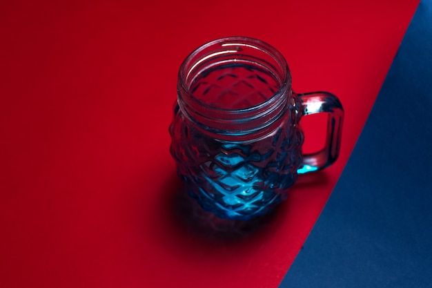 Gros plan vue de dessus de tasse en verre pour jus sur fond de couleurs rouges et bleues.