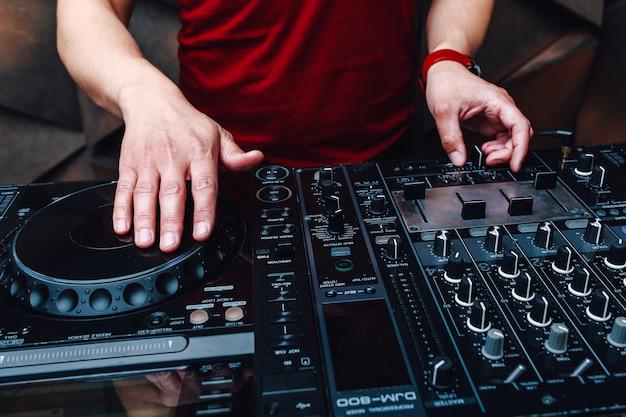 Gros plan vue dj mains sur mixer et disques vinyles