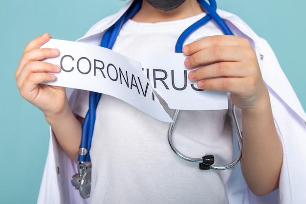 Gros plan, vue garçon peu tenant le coronavirus papier écrit sur bleu
