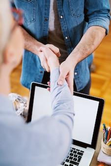 Gros plan sur la vue de se serrer la main après un entretien d'embauche réussi.