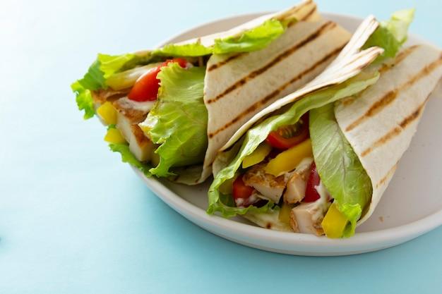 Gros plan wrap sandwich burrito avec du pain plat avec des légumes et de la viande blanche. espace de copie