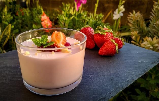 Gros plan de yaourt aux fraises avec des fraises sur le tableau noir