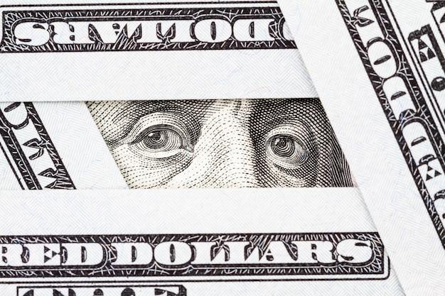 Gros plan des yeux de benjamin franklin entre les billets de cent dollars