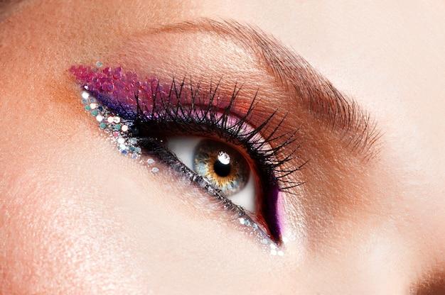 Gros plan des yeux de femme avec une belle mode maquillage rose vif