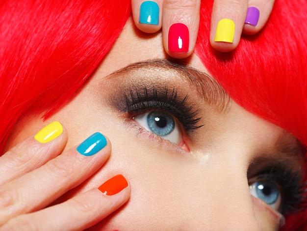Gros plan des yeux d'une fille avec des ongles multicolores brillants.