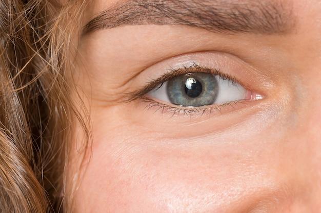 Gros plan des yeux gris sur le visage de la belle jeune fille caucasienne
