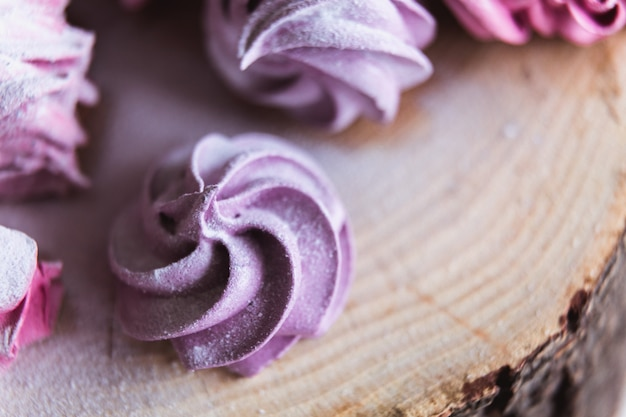 Gros plan de zephyr ou de guimauve rose coupé maison en sucre en poudre sur bois