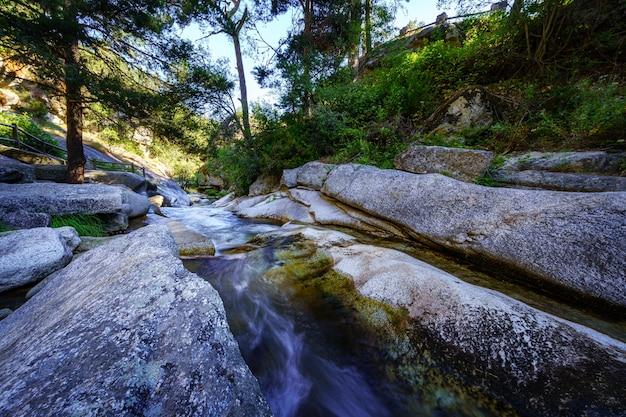 De gros rochers de granit avec l'eau de la rivière qui coule entre eux. navacerrada.