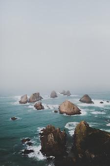 De gros rochers à nugget point ahuriri, nouvelle-zélande avec un fond brumeux