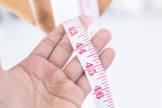 Gros ruban à mesurer dans la main de l'homme.