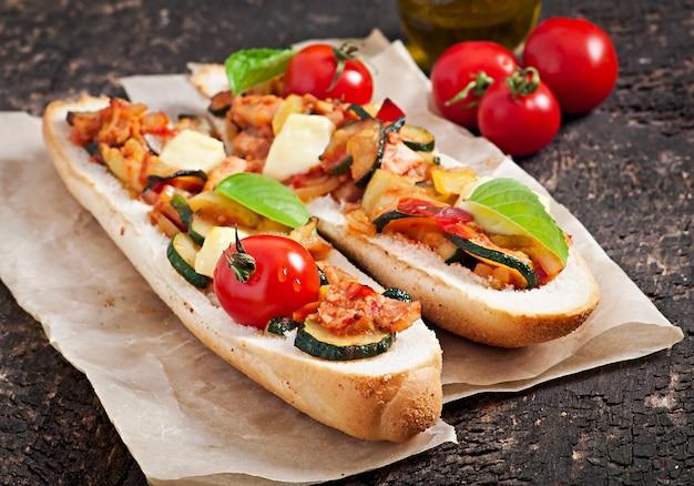 Gros sandwich aux légumes grillés au fromage et au basilic sur une vieille surface en bois