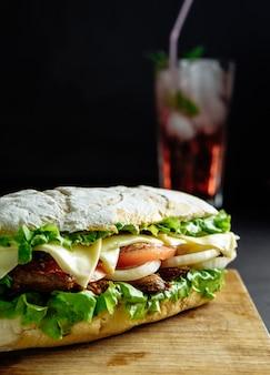 Gros sandwich avec cocktail boisson rose