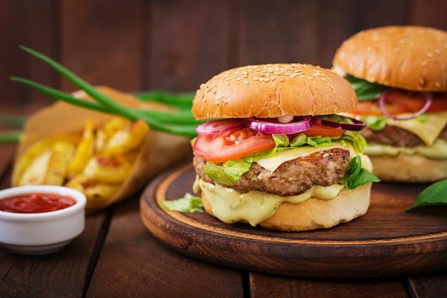 Gros sandwich - hamburger avec burger de boeuf juteux, fromage, tomate et oignon rouge sur table en bois