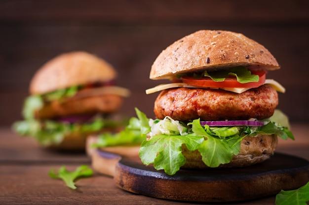 Gros sandwich - hamburger avec burger de poulet juteux, fromage, tomate et oignon rouge sur table en bois