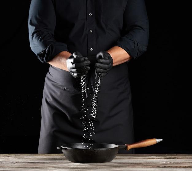 Le gros sel blanc est versé des paumes du chef