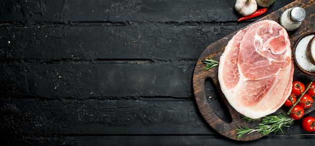 Gros steak de porc cru aux épices et légumes. sur un fond rustique noir.